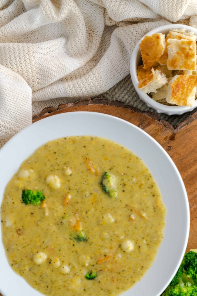 Instant Pot Broccoli Cheddar Gnocchi Soup with a side of bread pieces.