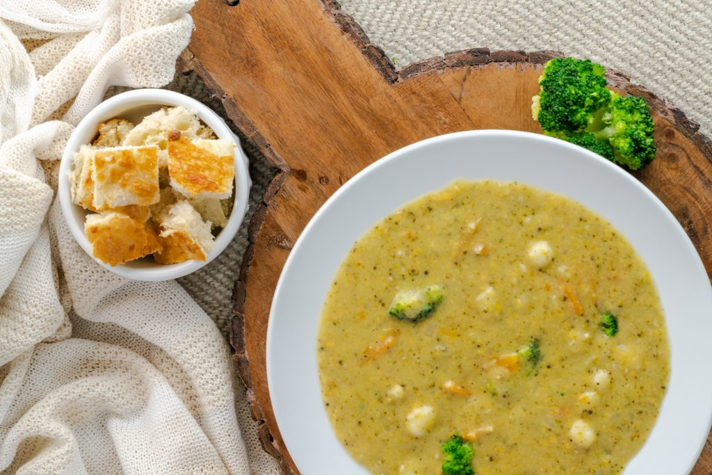 Broccoli and cheddar soup with bread pieces on the side.