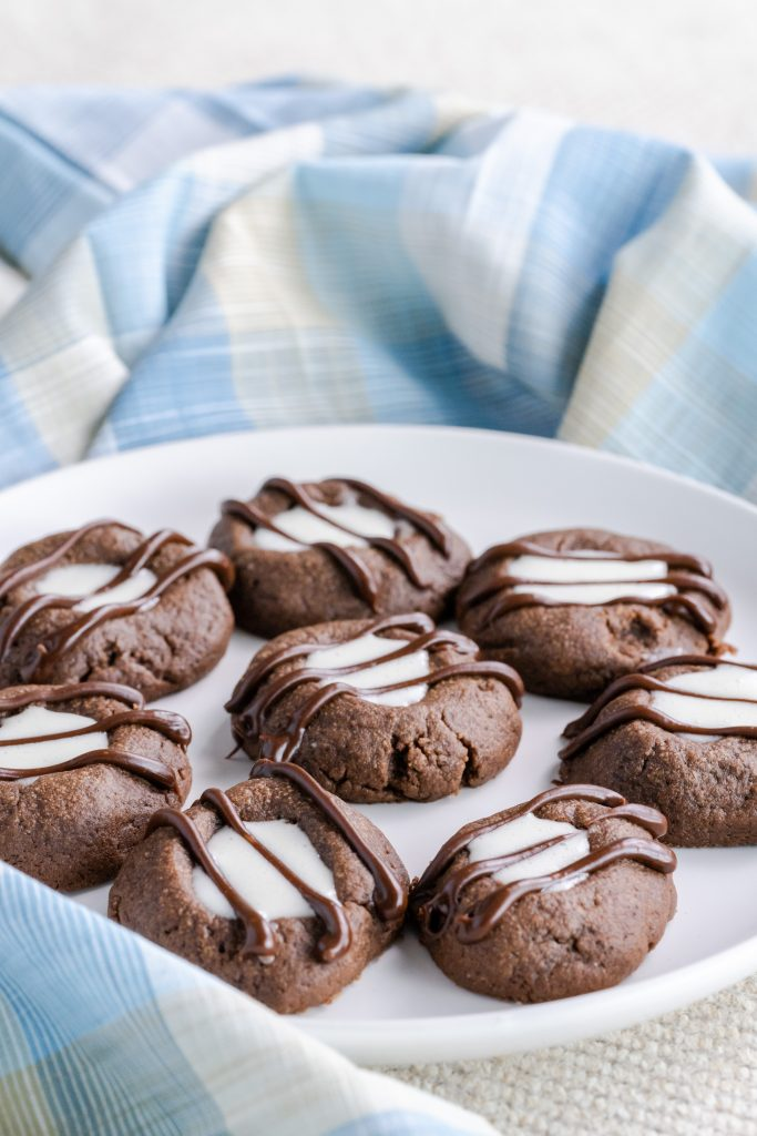 Chocolate thumbprint cookies filled with marshmallow creme and drizzled with chocolate on a white plate.