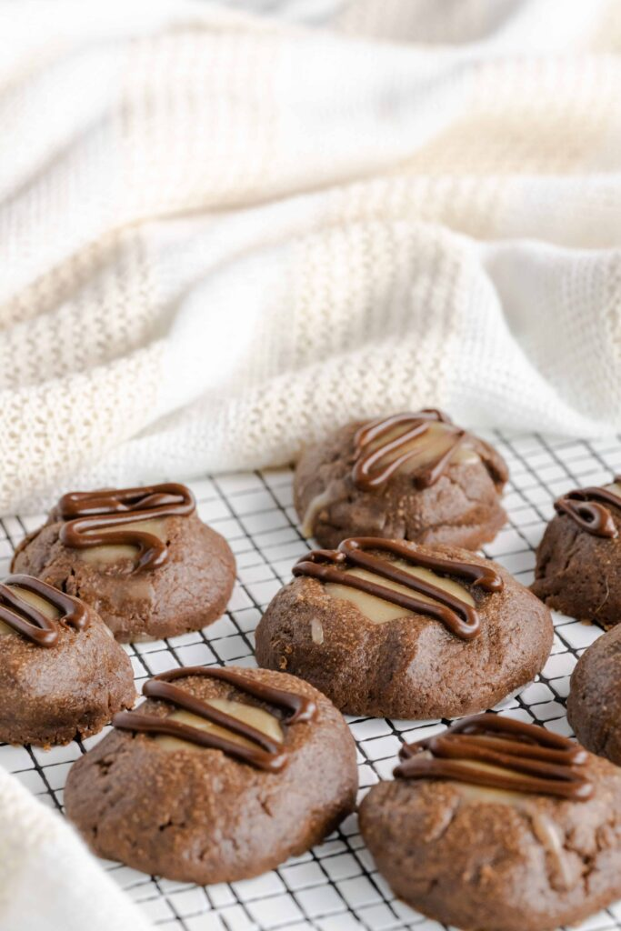 Peanut butter chocolate thumbprint cookies drizzled with chocolate on a plate.