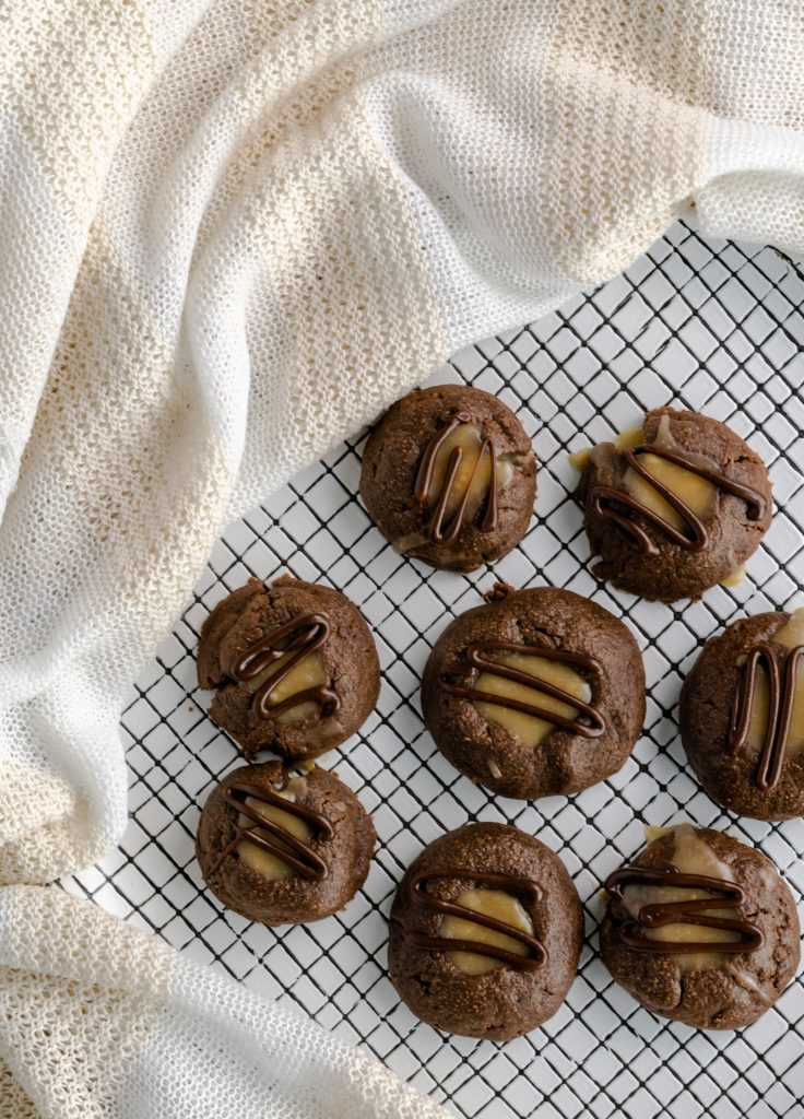 Chocolate thumbprint cookies on a plate lined with squares drizzled with chocolate.