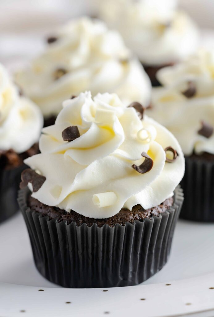 Chocolate cupcakes with chocolate buttercream garnished with milk chocolate and white chocolate curls.