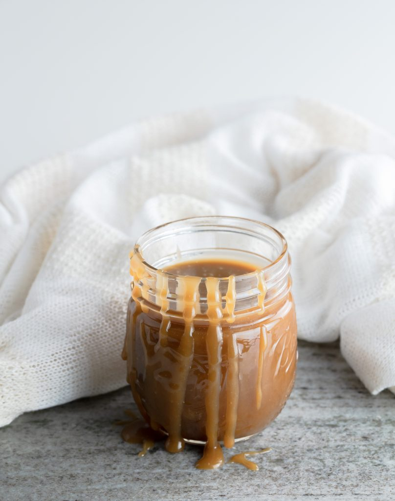 A jar of butterscotch sauce with the sauce spilled over the side of the har.