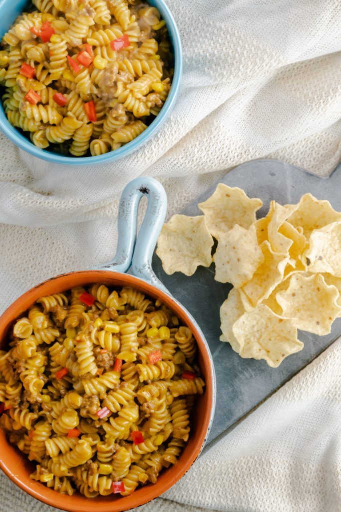 A serving of taco pasta with tortilla scoops on the side.
