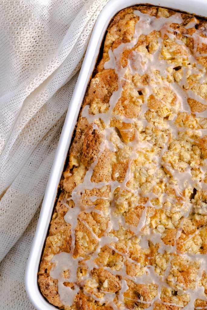 Apple crumb coffee cake in a baking dish with a vanilla glaze.