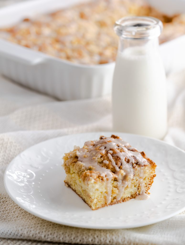 A slice of apple crumb coffee cake with a jar of milk.
