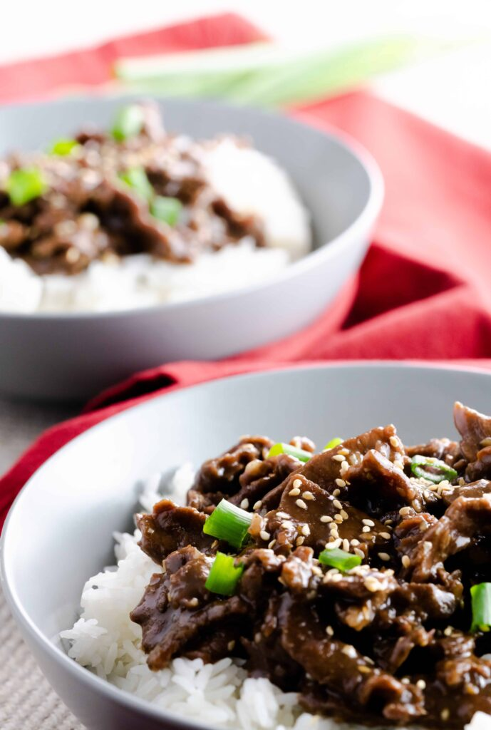 Garlic sesame beef topped with toasted sesame seeds and chopped scallions on a bed of rice.
