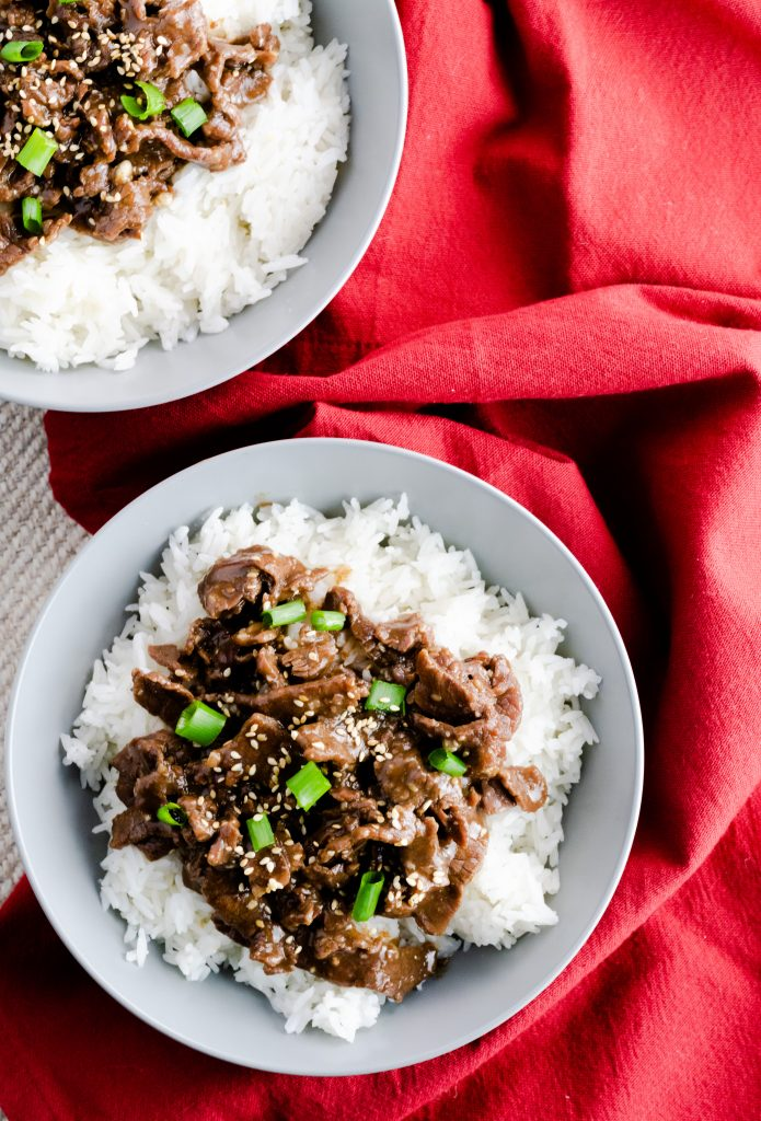 Two bowls of Garlic Sesame & Beef made with jasmine rice on a red napkin.