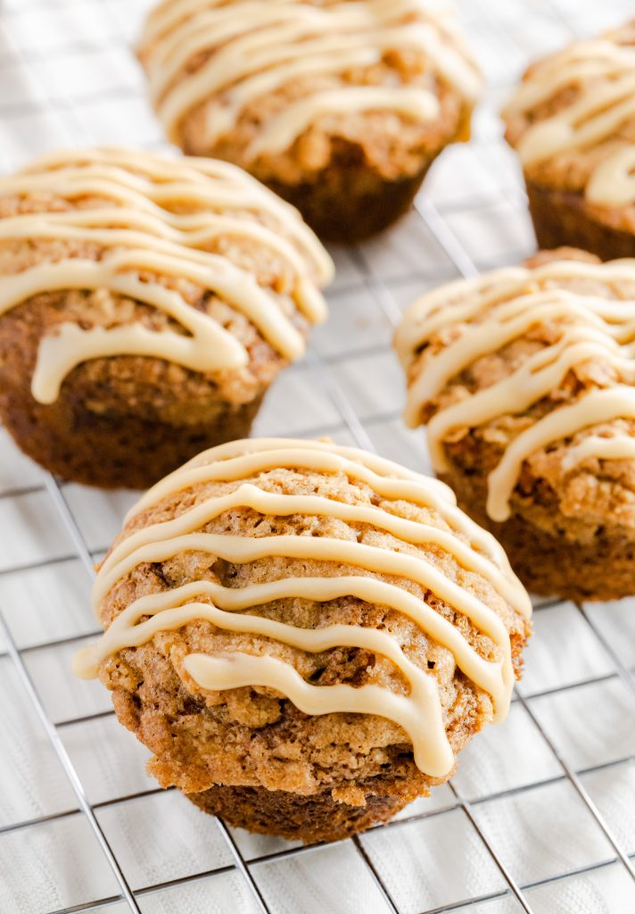 Moist and fluffy banana muffins topped with brown sugar and cinnamon crumb topping.  Drizzling the muffin tops is a caramel glaze.