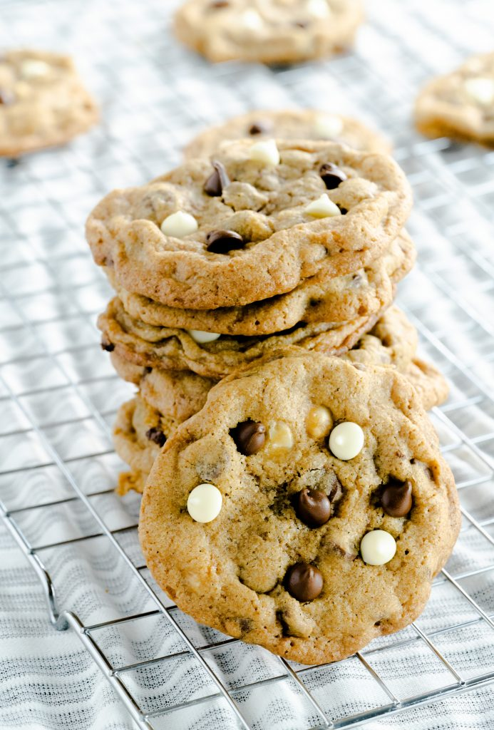 A stack of mocha cookies topped with milk and white chocolate chips.