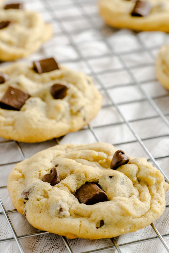 Soft batch chocolate chip cookies on a wire rack.