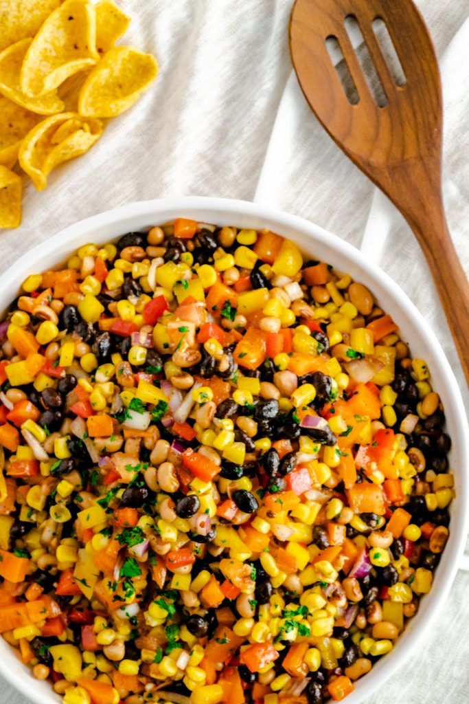 Black Bean corn salad in a large white bowl with Frito scoops.
