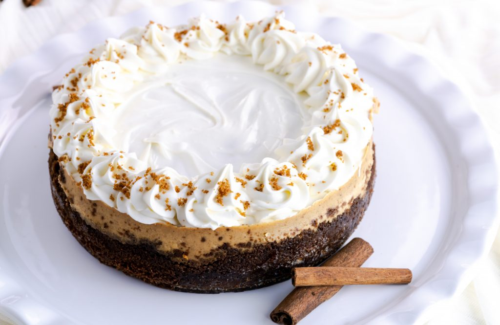 A whole gingerbread cheesecake decorated with homemade white chocolate mousse.