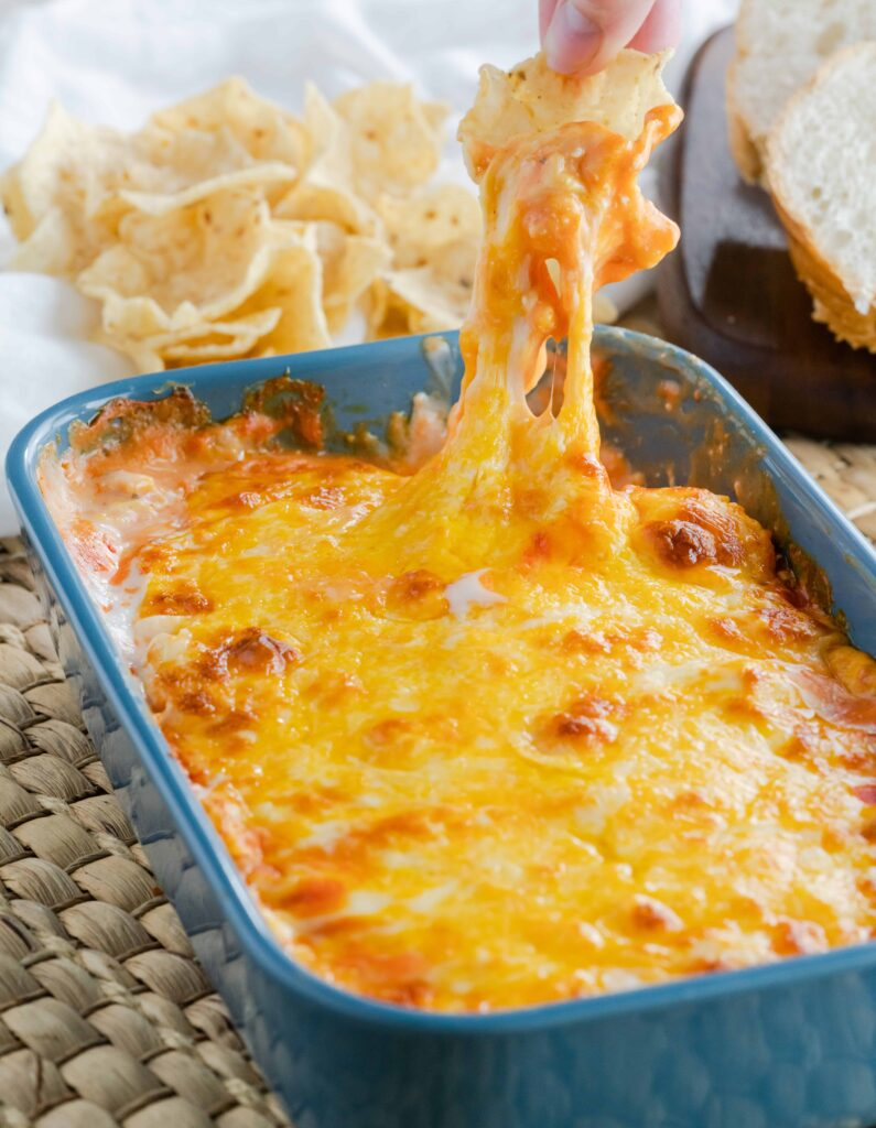 Buffalo Ranch Chicken Dip in a blue casserole dish being dipped with a tortilla scoop.