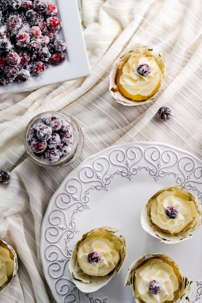 White chocolate cupcakes with white chocolate frosting and garnished with a frosted cranberry.