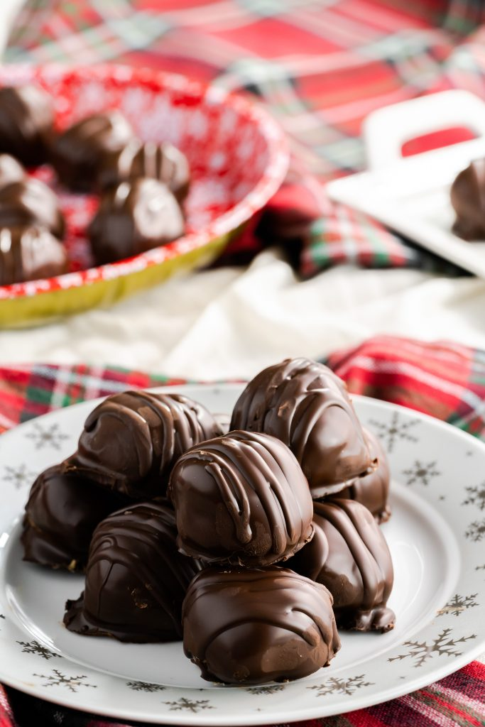 Peanut butter balls (buckeyes) stacked on a plate with chocolate drizzle for decoration.