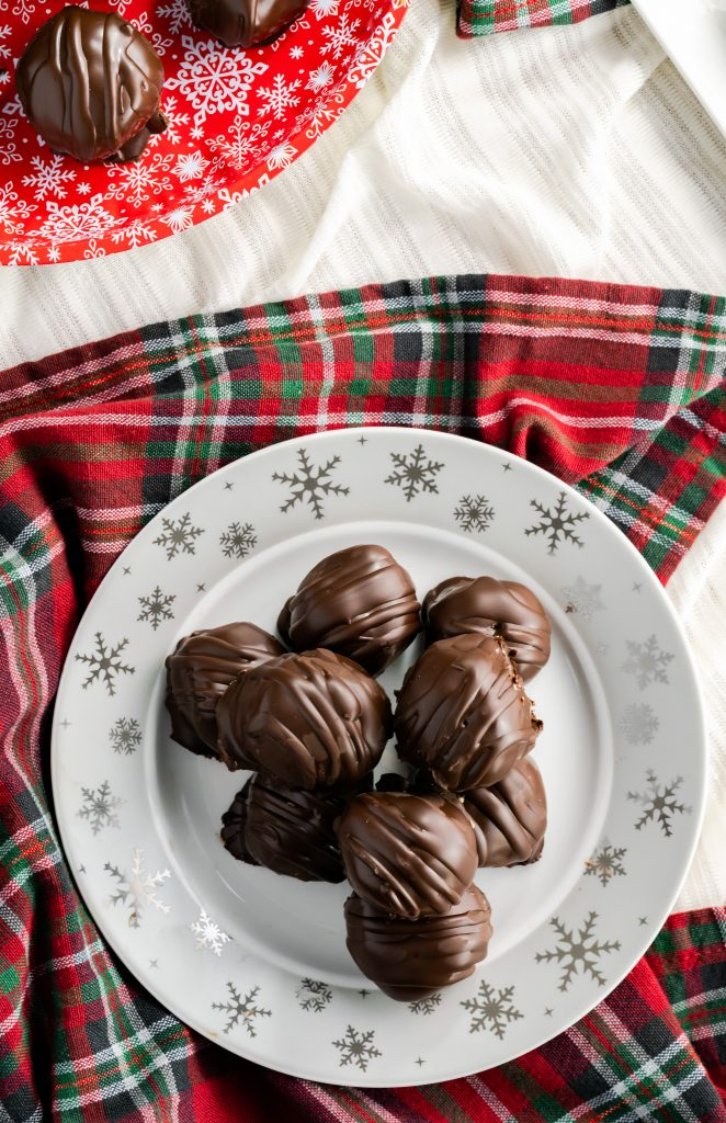 Platter of peanut butter balls sitting on a red and green decorative napkin.