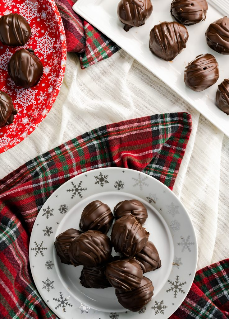 Peanut butter balls on a Christmas snowflake platter with a decorative Christmas napkin.