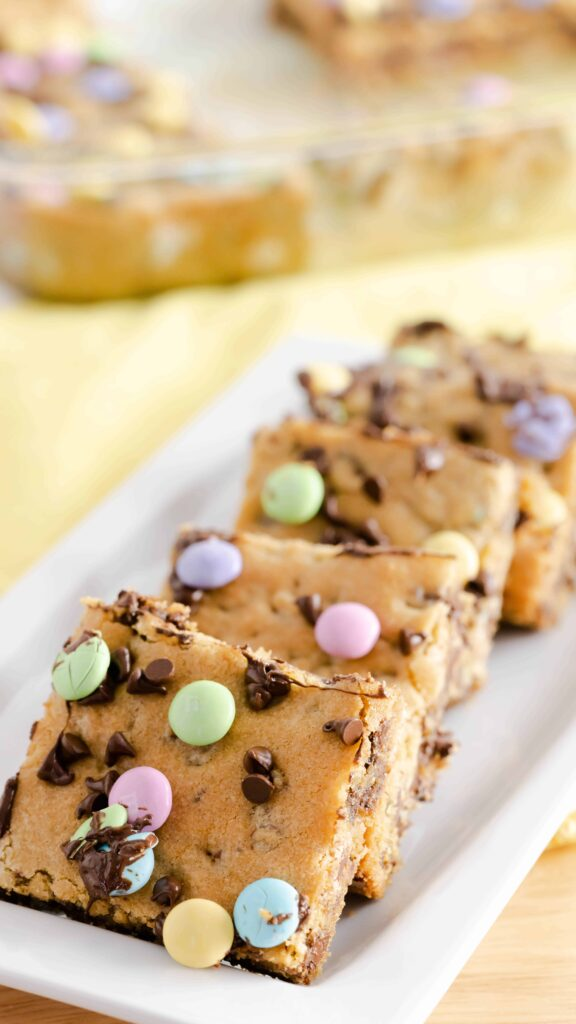 Chocolate Chip Cookie Bars cut into squares and resting on a white rectangular plate.