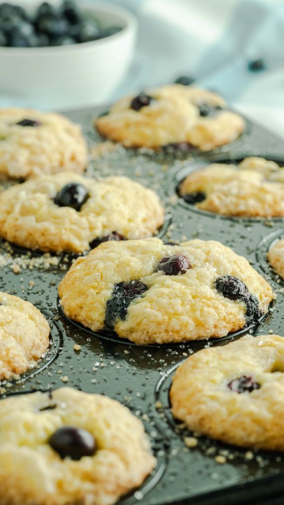 Side view of blueberry muffins in a muffin tin that has busted blueberries on top of the muffins.