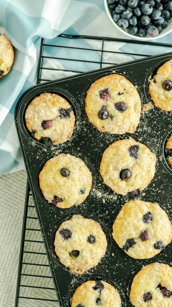 A dark muffin tin with cake mix blueberry muffins with a a bowl of fresh blueberries.