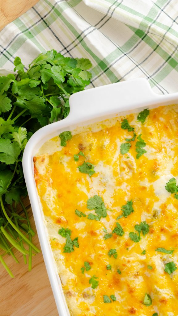 White chicken enchiladas in a white casserole dish.