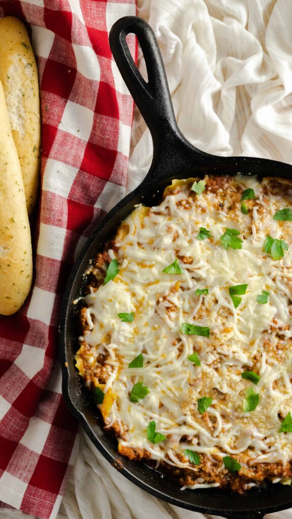 Easy skillet lasagna meal in a cast-iron skillet topped with melted cheese and fresh parsley.