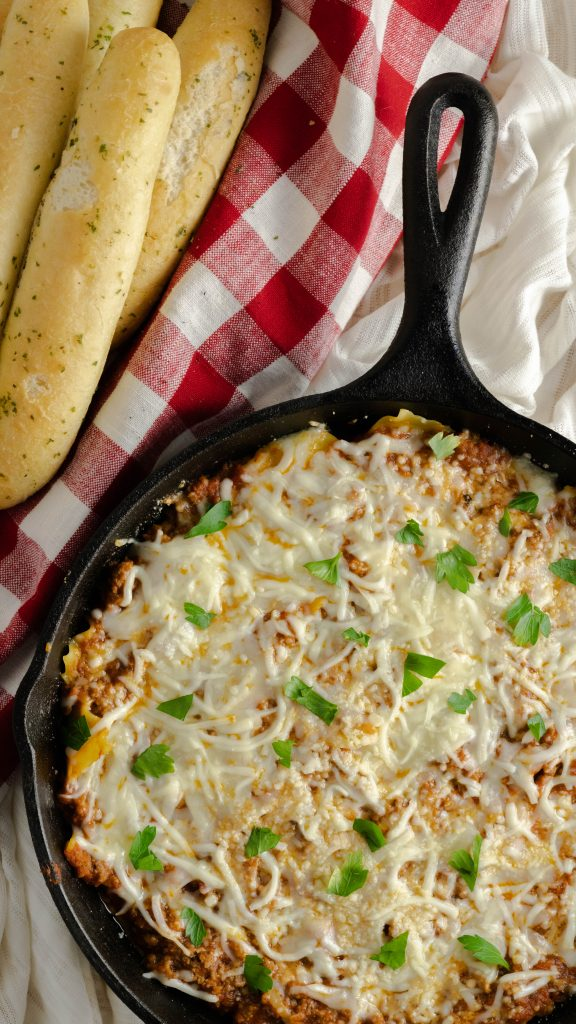 Easy skillet lasagna in cast iron skillet with melted cheese and parley with a side of breadsticks.