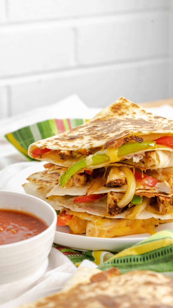 Chicken Fajita Quesadillas stacked with green peppers, onions, and seasoned chicken.