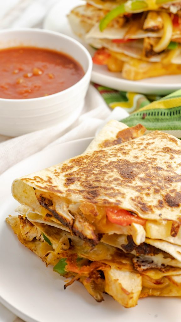 Quesadillas with seasoned chicken, julienned red peppers, onions, and cheese with a side of salsa for dipping.