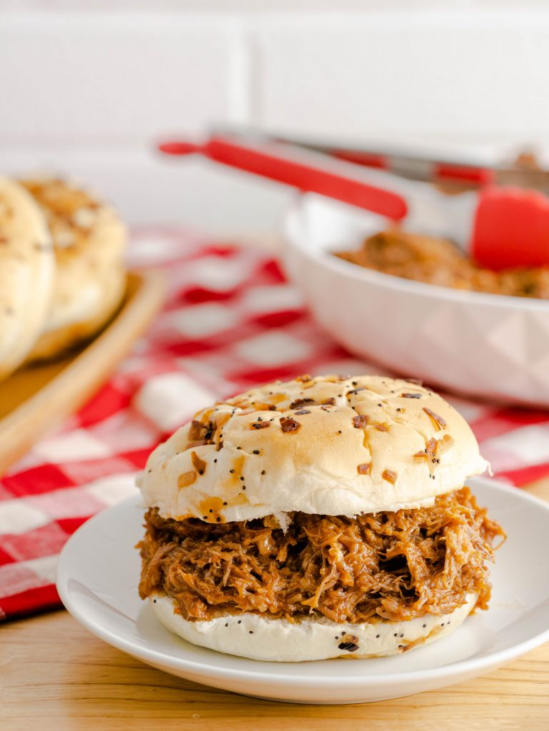 Root beer pulled pork in an onion and herb hamburger bun on a white plate.