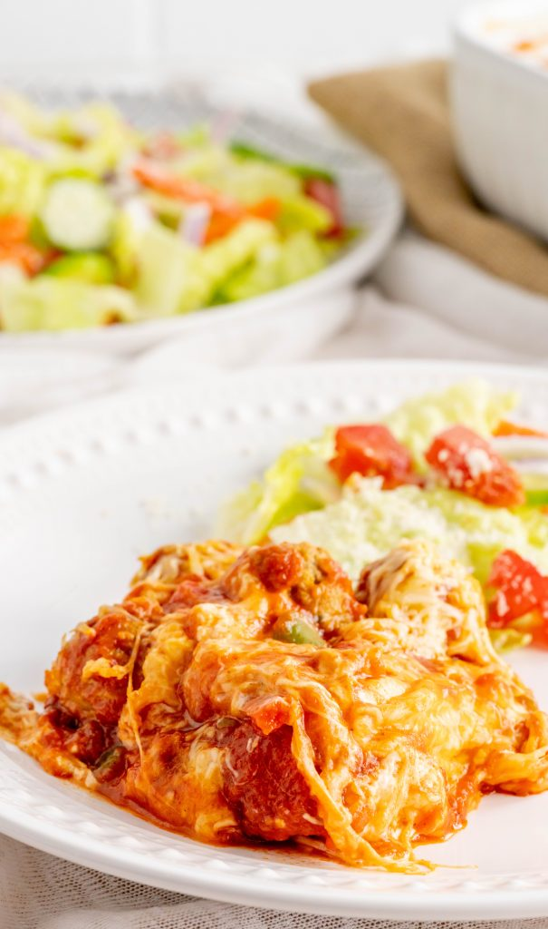 A plate of meatball casserole with a side salad.