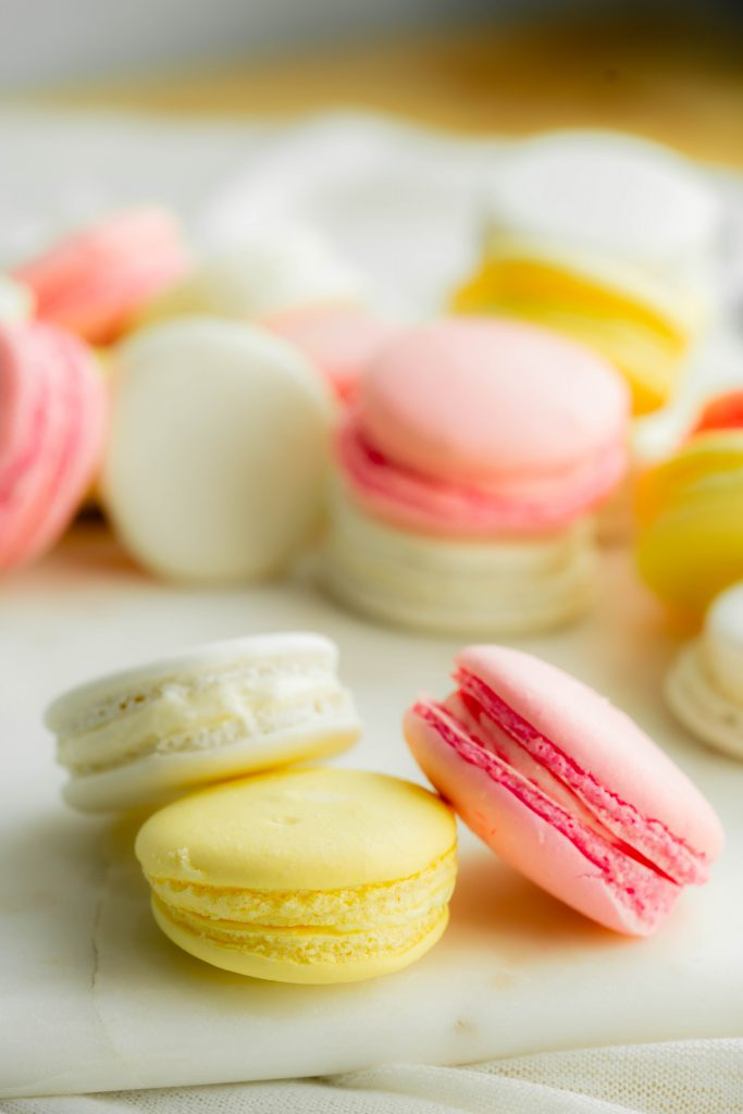 Pink, white, and yellow macarons on white marble board.