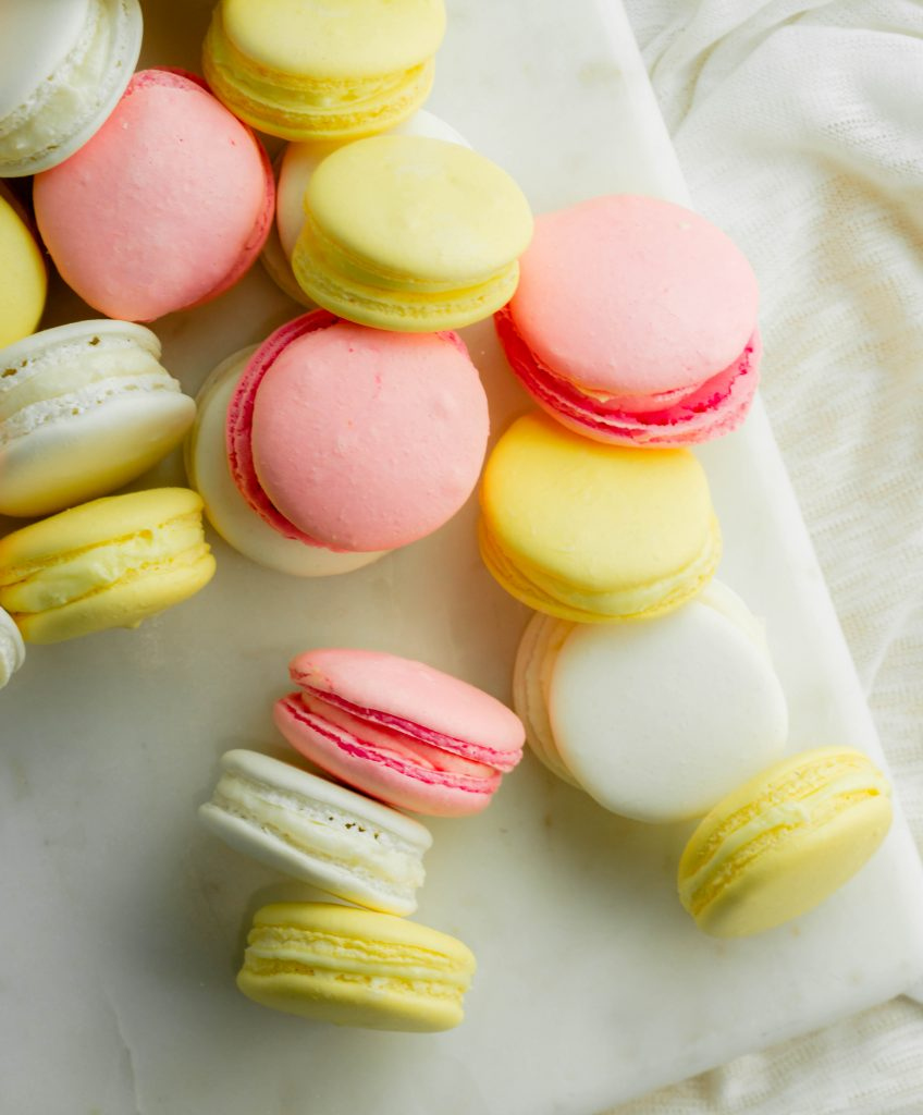 Strawberry, vanilla, and lemon macarons cookies scattered on marble board.
