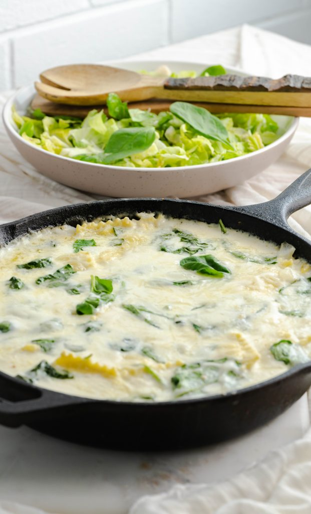 Spinach and Cheese Ravioli Skillet in a cast-iron skillet with a side salad of romaine lettuce.
