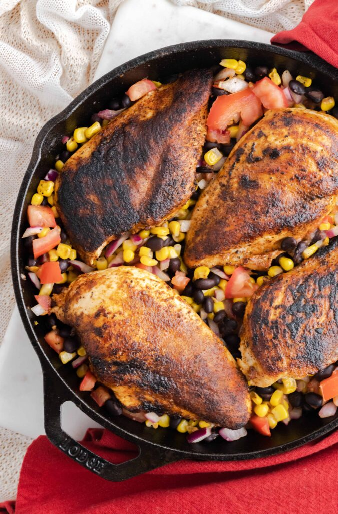 Blackened chicken in a cast iron skillet with bean salsa.