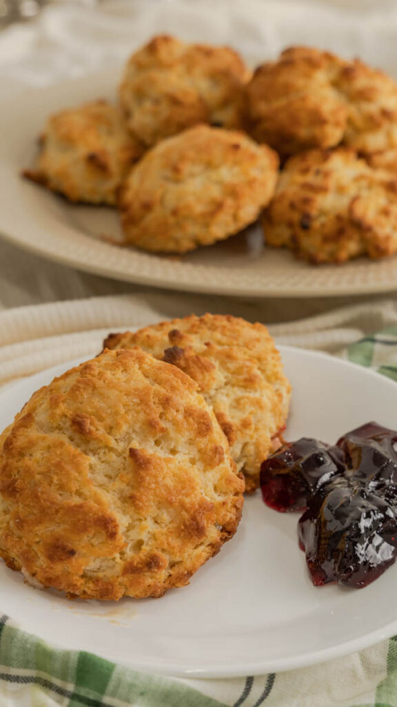 Two buttermilk drop biscuits on a plate served with grape jelly.