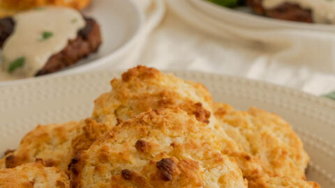 A plate of drop biscuits on a beige plate.