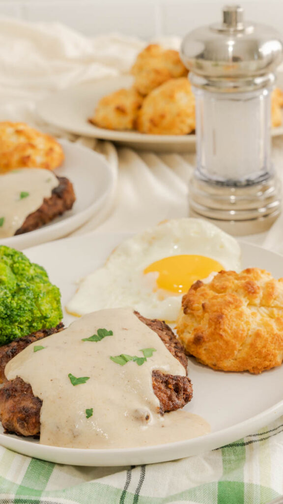 A drop biscuit on a plate with country fried steak covered with white gravy and garnished with parsley.