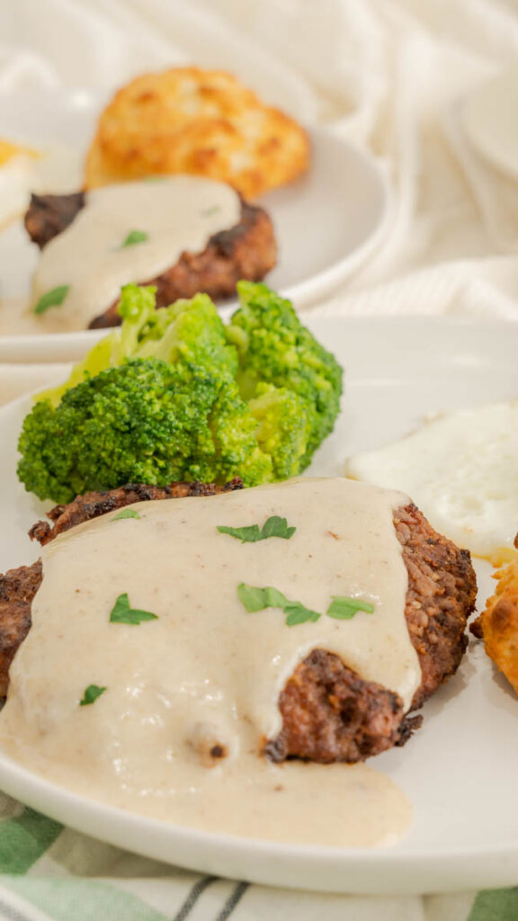 Country fried steak with gravy on a plate with broccoli in the background.