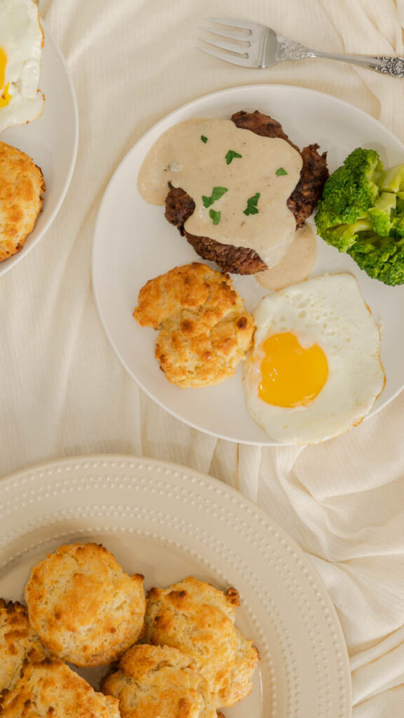 Top view of country fried steak smothered with white gravy with sunny side up egg and buttermilk drop biscuit on a plate.
